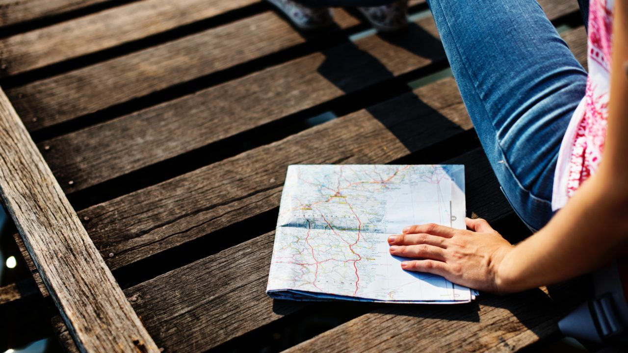 persona sentada sobre una superficie de madera oscura sostiene un mapa doblado en la mano