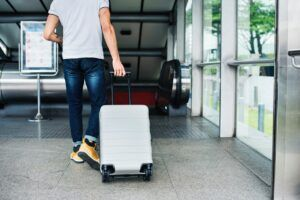 Hombre viaja con maleta en aeropuerto