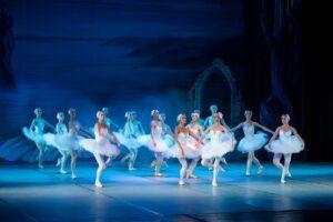 Bailarines de ballet representan una obra sobre un escenarios vistiendo tutús