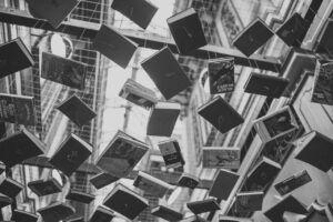 Libros colgando de cuerdas en el techo - foto en blanco y negro