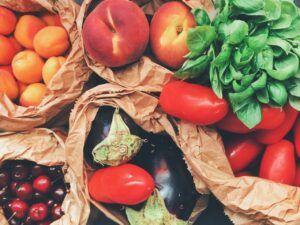 Frutas y verduras frescas dentro de bolsas de papel sobre una mesa