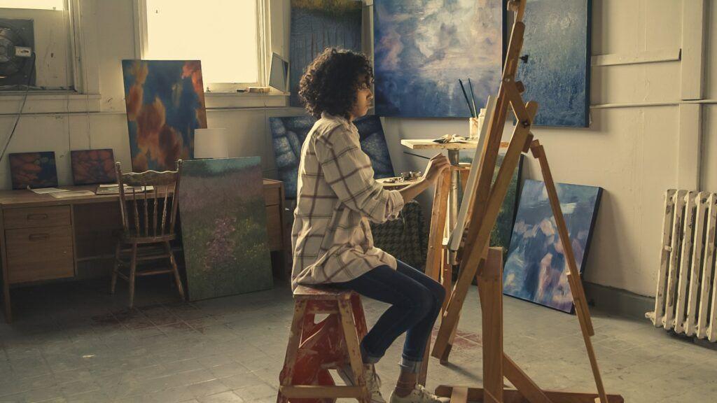 Chica joven sentada sobre un taburete pinta sobre un lienzo en una sala repleta de cuadros abstractos coloridos ya acabados.