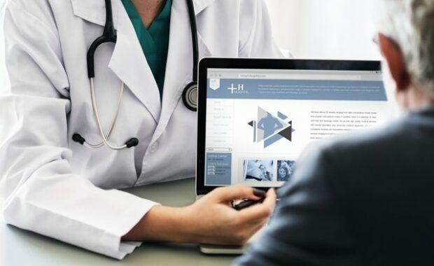 Doctor informando al paciente mientras señala a un ordenador