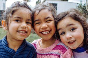 Tres niñas pequeñas sonríen a la cámara
