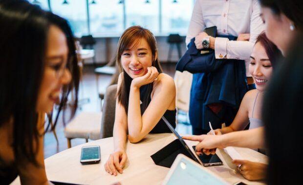 varios jóvenes se reúnen alrededor de una mesa redonda para trabajar juntos