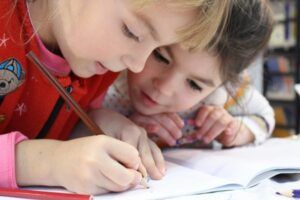 dos niñas pequeñas escriben concentradas en un cuaderno