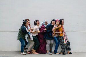 Mujeres de difernetes orígenes étnicos abrazándose y riéndose junto a una pared gris