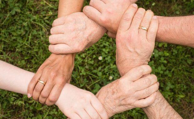 cinco manos unidas sobre un fondo de césped