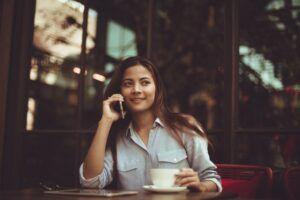 Chica asiática sonriente sentada en la mesa de una cafetería se toma un café mientras habla por teléfono