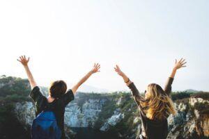 Dos chicas de espaldas alzan las manos en señal de victoria mientras llevan unas mochilas en un entorno natural rocoso