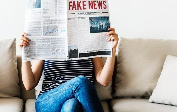 """Persona sentada en un sofá sostiene un periódico en el que se lee """"Fake News"""""""