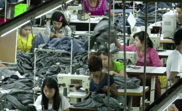 Mujeres asiáticas trabajan en una fábrica de costura en condiciones desfavorables