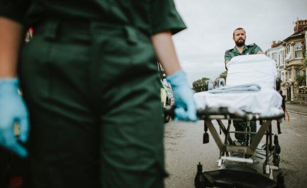 Equipos de emergencias van a atender a alguien empujando una camilla y llevando guantes de látex