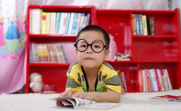niño con gafas lee en una biblioteca