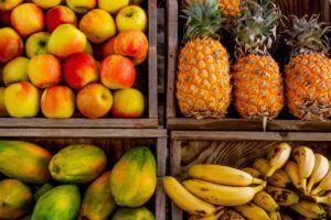 Cuatros cestas llenas de fruta: manzana, papaya, piña y plátano